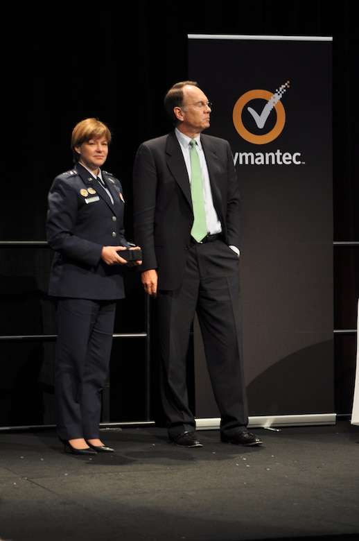 WASHINGTON, D.C. - Maj. Gen. Suzanne Vautrinot, 24th Air Force and Air Forces Cyber commander, stands next to Steve Bennett, Symantec chairman, president and chief executive officer, after he presents her with one of Symantec's six 2012 Cyber Awards at the 2012 Symantec Government Symposium, Nov. 7. The annual award recognizes leaders who exemplify government cyber security excellence through their contributions to programs that protect national and global data and systems. (U.S. Air Force photo by Christine D. Millette)
