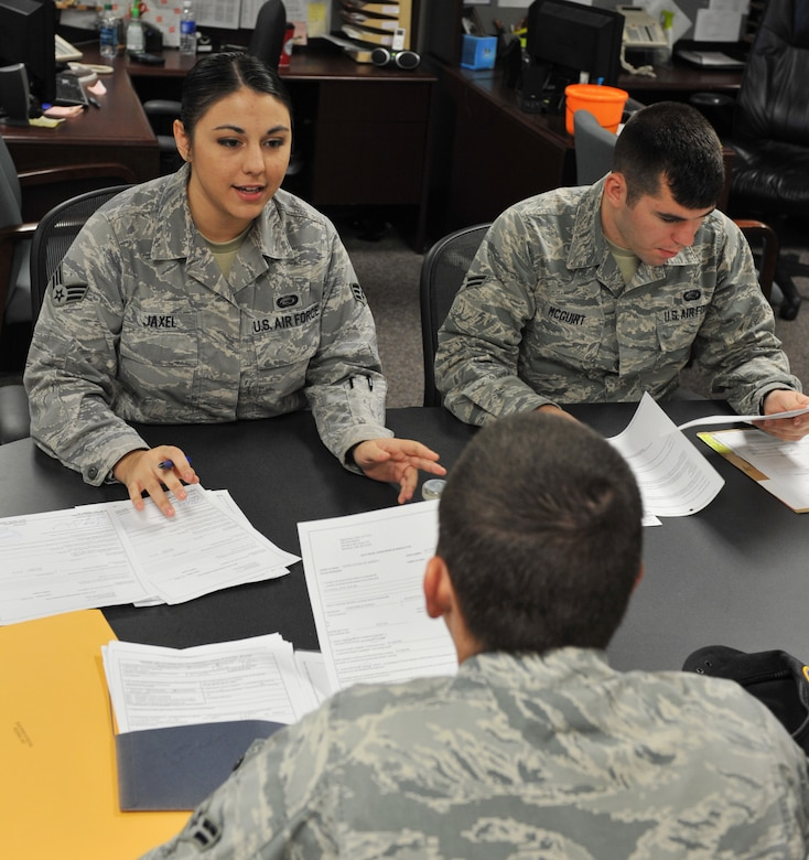 Senior Airman Lindsey Jaxel, and Airman 1st Class Jordan McGuirt, 509th Force Support Squadron career development representatives, assist Airman 1st Class Justin Tallman, 509th Security Forces Squadron, with outprocessing paper work at the Career Development Office Oct. 31. Prior to base permanent change of station, members are required to complete the necessary paper work before they can officially outprocess. (U.S. Air Force photo/Heidi Hunt) (Released)