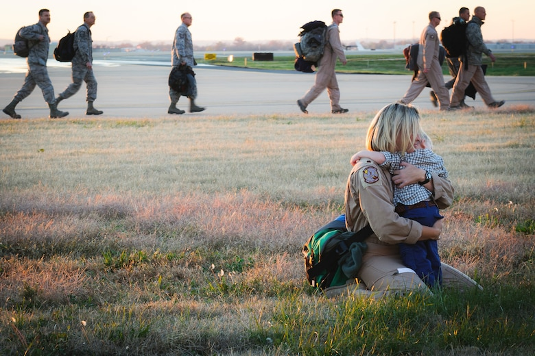 Maj. Jennifer Helton, a navigator for the 165th Airlift Squadron, hugs her son next to the flight line of the Kentucky Air National Guard Base in Louisville, Ky., Nov. 12, 2012. Helton was one of 58 Kentucky Air Guardsmen returning from a four-month deployment to the Persian Gulf region. (U.S. Air Force photo by Airman Basic Joshua L. Horton)