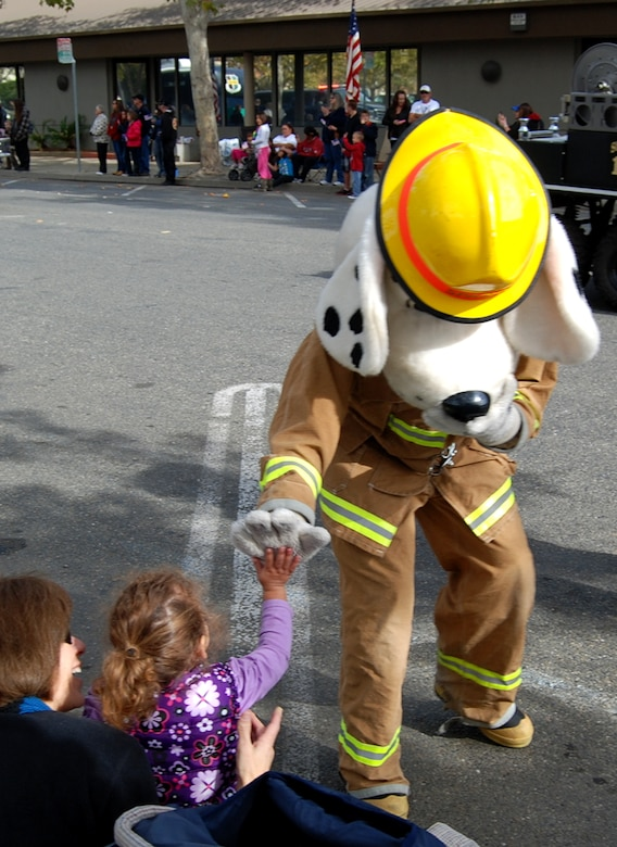 Sparky the Fire Dog gives a high five to a girl sitting along the parade route during the Yuba-Sutter Veterans Day Parade in Marysville, Calif., Nov. 11, 2012. More than 400 Team Beale Airmen participated in the parade. (U.S. Air Force photo by Capt. Brian Wagner/Released)