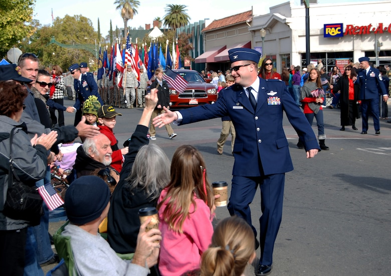 Col. Phil Stewart, 9th Reconnaissance Wing commander, shakes hands along the parade route during the Yuba Sutter Veterans Day Parade in Marysville, Calif., Nov. 11, 2012. More than 400 Team Beale Airmen participated in the parade. (U.S. Air Force photo by Capt. Brian Wagner/Released)