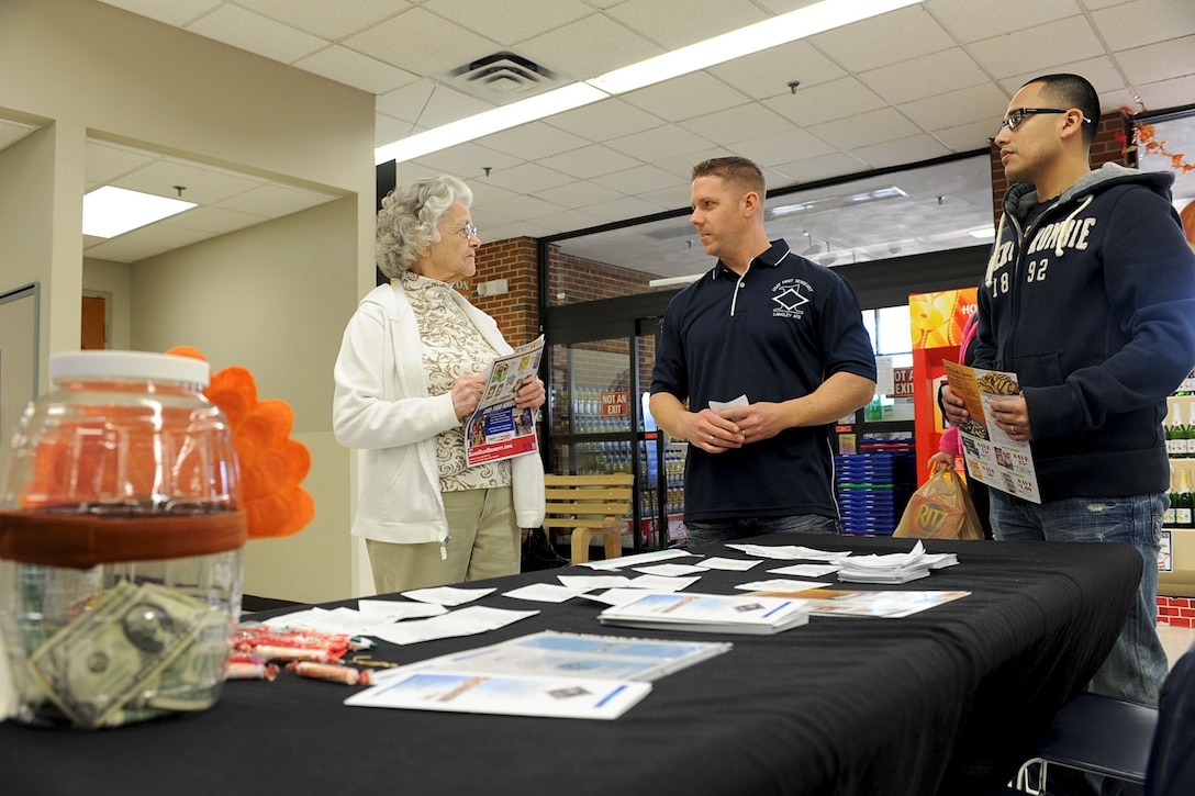 U.S. Air Force Master Sgt. James Kaufman, 438th Supply Chain Operation Squadron first sergeant (center) and Staff Sgt. Eric Perez, 438th SCOS F-16 weapons system management flight supervisor, inform Audra Caldwell how to donate to the Operation Warmheart organization at the Base Exchange, Langley Air Force Base, Va., Nov. 9, 2012. Operation Warmheart is an organization run by first sergeants to help Airmen in need, especially during the holidays. (U.S. Air Force photo by Staff Sgt. Ashley Hawkins/Released)