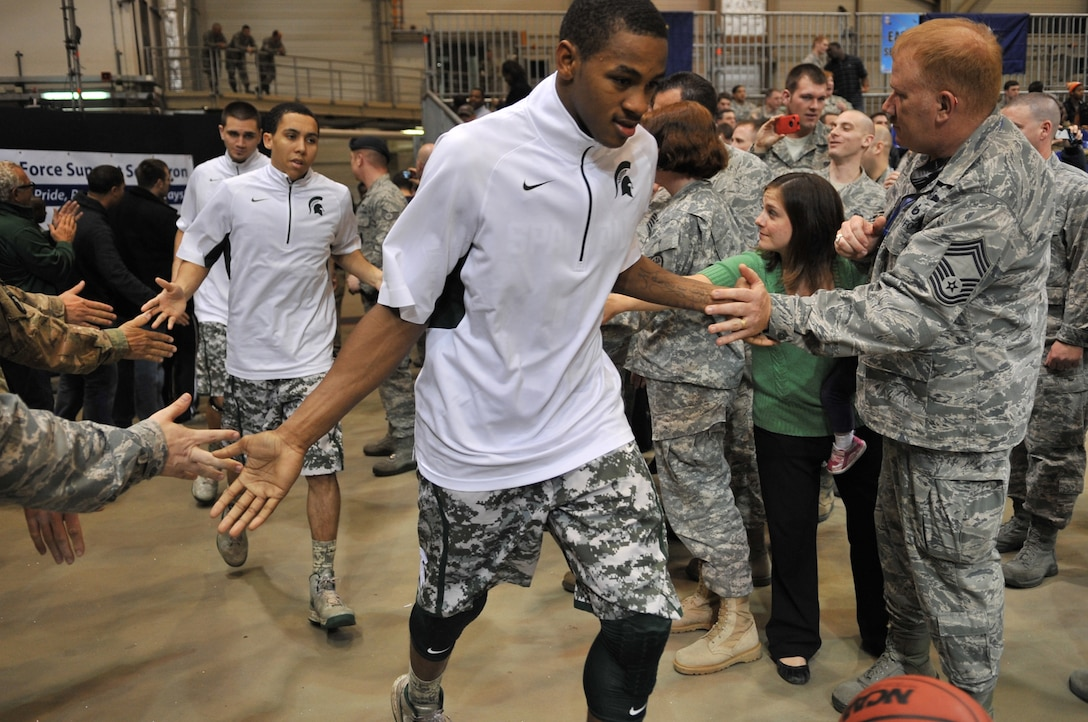 Michigan State Spartan players slap hands of service members after half time during the Armed Forces Classic basketball game between Michigan State Spartans and University of Connecticut Huskies at Ramstein Air Base, Germany, Nov. 10, 2012.  The Huskies overcame the Spartans 66-62. (U.S. Air Force photo/Master Sgt. Wayne Clark)