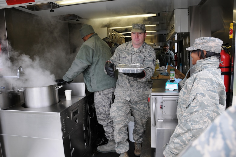 Tech. Sgt Marx from the 113th Force Support Squardon brings hot food to awaiting airman during a new mobile field kitchen during a demonstration at Joint Base Andrews, Md., Nov. 3. The Disaster Relief Mobile Kitchen Trailer  can deploy to natural disaster sites to provide hot meals to relief workers and Airmen working in austere conditions. (U.S. Air force photo by Airman 1st Class Sumena Leslie/Released)