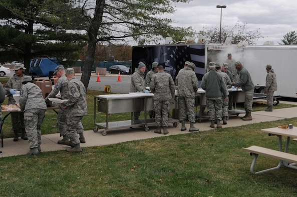 Airman from the 113th Wing wait in line to be fed during a new mobile field kitchen during a demonstration at Joint Base Andrews, Md., Nov. 3. The Disaster Relief Mobile Kitchen Trailer  can deploy to natural disaster sites to provide hot meals to relief workers and Airmen working in austere conditions. (U.S. Air force photo by Airman 1st Class Sumena Leslie/Released)