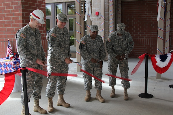 Lt. Col. Chamberlayne, Brig. Gen. Roberts and others cut the ribbon on the Quad DFAC.