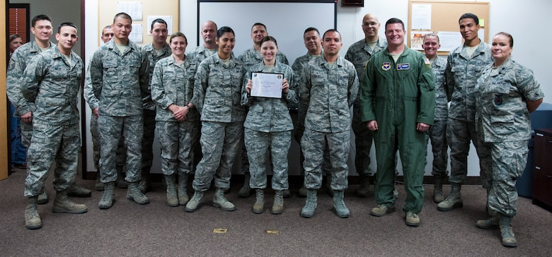 """Members of Laughlin's 47th Operations Support Squadron pose for a photo after receiving an award for being the top power producers in the """"Sweat for Power"""" competition Nov. 13, 2012. The 47th OSS generated 900 watt-hours of power on five retrofitted elliptical machines at the Losano Fitness Center at Laughlin Air Force Base, Texas. The competition was one of the many activities the 47th Civil Engineer Squadron sponsored as part of Laughlin's 2012 Energy Action Month. (U.S. Air Force photo/Airman 1st Class Nathan Maysonet)"""