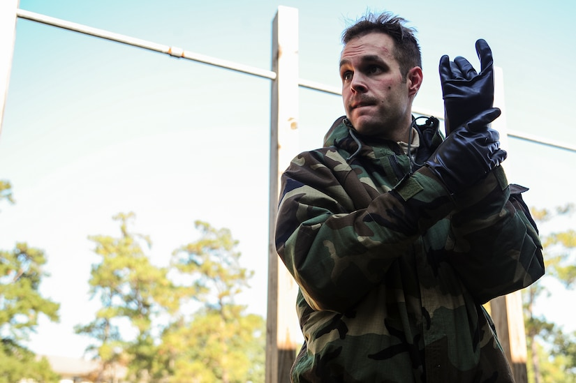 Senior Airman James Richardson, 1st Combat Camera Squadron photographer, simulates wiping decontaminating his gloves during  a Chemical, Biological, Radiological, Nuclear, Explosives Defense Survival Skills training scenario Nov. 8, 2012, at Joint Base Charleston - Air Base, S.C.  1st CTCS participates in various types of training to stay mission ready as they often document first responders in humanitarian relief efforts and disasters. (U.S. Air Force photo by/Staff Sgt. Rasheen Douglas)