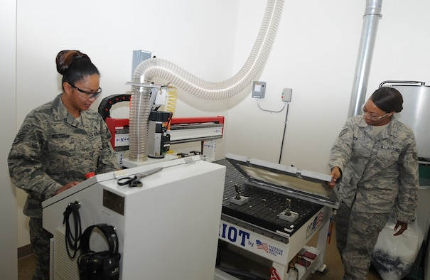 Staff Sgt. Joy Victoria and Staff Sgt. Maria Cook, use the milling machine to cut arch support inserts, Oct. 9 at the David Grant Medical Center brace shop. (US Air Force photo/Staff Sgt. Liliana Moreno)