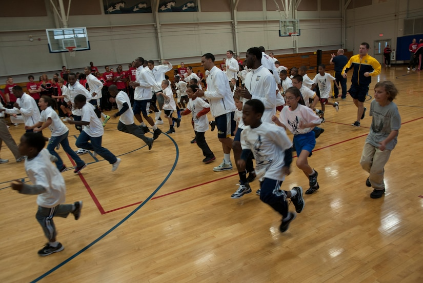 Basketball players from Ohio State, Notre Dame and Marquette University warm up with military children during a Hoops from Home Clinic Nov. 8, 2012, at Joint Base Charleston, S.C. Hoops from Home is a non-profit organization providing a basketball camp/clinic experience to the children of military families across the world. It provides the children with an opportunity to work with players and coaches and highlight the benefits of team sports, physical activity and commitment. (U.S. Air Force photo/Airman 1st Class Ashlee Galloway)