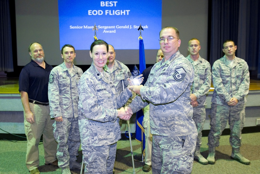 Master Sgt. Brian a. Fleming accepts the Senior Master Sgt. Stryzak Award for Outstanding EOD Flight presented by Lt. Col. Susan Riordan-Smith.