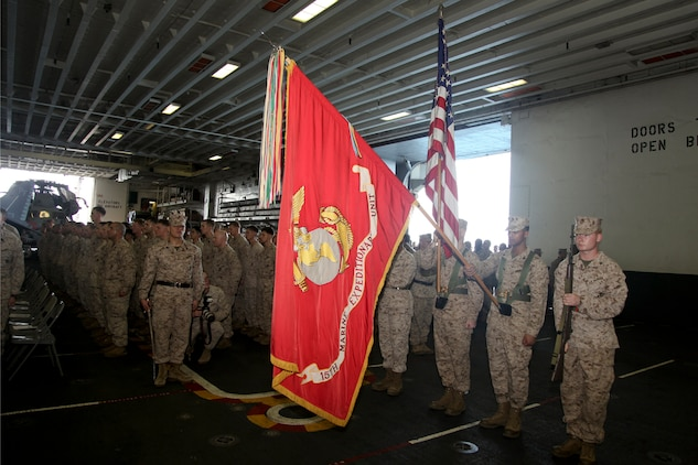 Marines with the 15th Marine Expeditionary Unit render honors during the playing of the national anthem at the 237th Marine Corps Cake Cutting Ceremony held in the hangar bay of the USS Peleliu, Nov. 10. The 15th MEU is deployed as part of the Peleliu Amphibious Ready Group as a theater reserve and crisis response force throughout U.S. Central Command and the U.S. 5th Fleet area of responsibility.