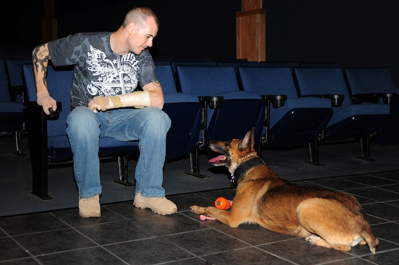 Staff Sgt. Leonard Anderson, 59th Patient Squadron, Lackland Air Force Base, Texas, talks to Azza, 354th Security Forces Squadron military working dog, at the base theater Oct. 17, 2012, Eielson Air Force Base, Alaska. Anderson worked with Azza, an 8-year-old Belgian Malinois, for over a year while he was assigned to the 354th SFS MWD section. (U.S. Air Force photo/Airman 1st Class Zachary Perras)