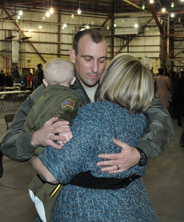 Master Sgt. Gabriel Richardson, an Air Surveillance Technician assigned to the 970th Airborne Air Control Squadron, embraces wife Candice and his six-month-old son for the first time. Richardson returned Sunday with 89 reservists from the 513th Air Control Group after a six-month deployment to Southwest Asia. Collin Richardson was born just a few days after Master Sgt. Richardson left on the deployment. (U.S. Air Force Photo by Capt. Jon Quinlan)