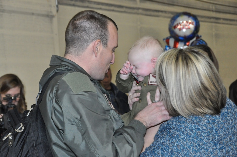 Master Sgt. Gabriel Richardson, an Air Surveillance Technician assigned to the 970th Airborne Air Control Squadron, holds his 6-month-old son for the first time. Richardson returned Sunday with 89 Reservists from the 513th Air Control Group after a 6-month deployment to Southwest Asia. Collin Richardson was born just a few days after Master Sgt. Richardson left on the deployment. (U.S. Air Force Photo byTech. Sgt. Sandra Hatton)