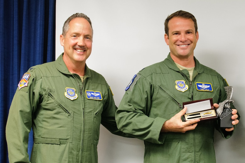 Col. Greg Nelson, commander of the 123rd Airlift Wing, presents Lt. Col. Todd Lally with the 2011 Air National Guard Outstanding Individual for Flight Safety Award during a ceremony at the Kentucky Air National Guard Base in Louisville, Ky., on May 19, 2012. Lally, chief of the wing safety office, earned the honor for his exceptional dedication to the safety community, according to the National Guard Bureau. (U.S. Air Force photo by Senior Airman Maxwell Rechel)