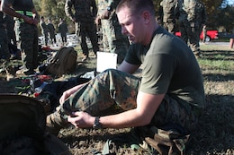 Fatigue starts to set in as Sgt. Michael Gannon, an Extract Marine assigned to React Company with the Chemical Biological Incident Response Force, as he changes into the next uniform after completing a three-mile run in protective MOPP gear and a gas mask. It was the second of three, three-mile runs in the CBIRF Commander's Challenge on Nov. 6. (Official Marine Corps photo by Sgt. Frances L Goch, Released)