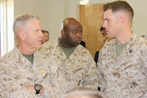 The 35th Commandant of the Marine Corps, General James F. Amos, Chief Warrant Officer Five Domah W. Diggs and Staff Sergeant Matthew W. Burks discuss the Chemical Biological Radiological and Nuclear (CBRN) School's mission while observing students learn to conduct CBRN hazard prediction at Fort Leonard Wood Missouri on October 18, 2012.