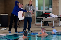 Megan Bradshaw-Downing, the lead aquatic exercise assistant at WWBn. West (left), and Michael F. Kleinert, a watersports specialist at WWBn. West (right), demonstrate fundamental techniques of swimming to detachment leaders at the Hope and Care Center Lap Pool here Nov. 15.