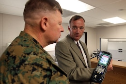 Mike Stefenyshyn, from the Base Access Control branch, gives Maj. Gen. James A. Kessler (center), commanding general of Marine Corps Installations Command and assistant deputy commandant of installations and logistics, a brief on the new hand-held scanners and Rapid Gate software that are being used at entry-points at Camp Pendleton Nov. 8.
