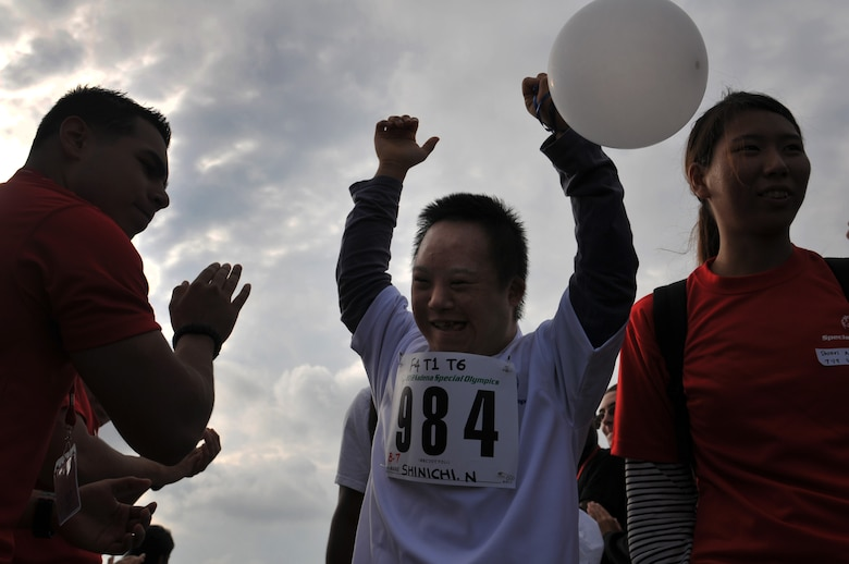 Shinichi Nakamura, an athlete participating in the the 13th annual Kadena Special Olympics arrive as thousands of attendees cheer them on as part of the KSO opening ceremonies on Kadena Air Base, Japan, Nov. 17, 2012.  More than 1,500 artists and athletes participated in a variety of events ranging from 200 and 300 meter races, tennis skills and floor hockey to soccer skills and ground golf during the 13th Annual KSO. This year marks the 13th Annual KSO, a sporting event dedicated to enriching the lives of special-needs individuals while strengthening U.S. - Okinawa relationships. (U.S. Air Force photo/Tech. Sgt. Jocelyn Rich)