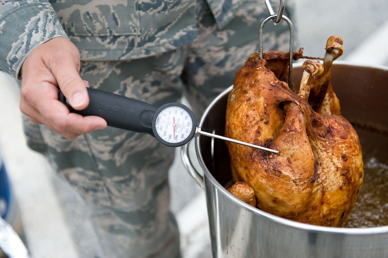 A thermometer is inserted into a turkey after it is removed from a turkey fryer Nov. 16, 2012, at Dover Air Force Base, Del. The oil temperature in the turkey fryer should be between 325 and 350 degrees while the internal meat of the bird should be between 175 and 180 degrees. (U.S. Air Force photo by Roland Balik)