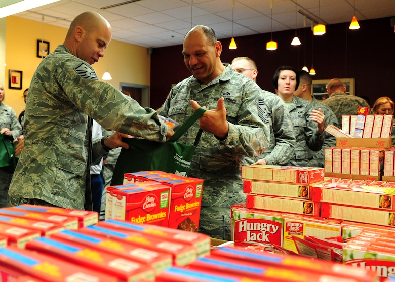 Master Sgt. Jason Davis, 489th Reconnaissance Squadron first sergeant, packs food in a bag held by Chief Master Sgt. Robert White, 9th Reconnaissance Wing command chief, Nov. 16, 2012, at Beale Air Force Base, Calif. The food will be delivered to Airmen for Thanksgiving, kicking off the holiday season for Operation Warm Heart, a program supporting Airmen and their families during times of need. (U.S. Air Force photo by Senior Airman Shawn Nickel/Released)