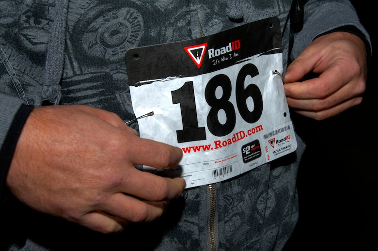 U.S. Air Force Master Sgt. Kelly Moose, 1st Aircraft maintenance squadron first sergeant, pins on his number for the Langley First Sergeants Council 5K Fun Run Walk to benefit Operation Warmheart, at Langley Air Force Base, Va., Nov. 16, 2012. Operation Warmheart supports Langley Airman and their families year round. (U.S. Air Force photo by Airman 1st Class Victoria Taylor/Released)