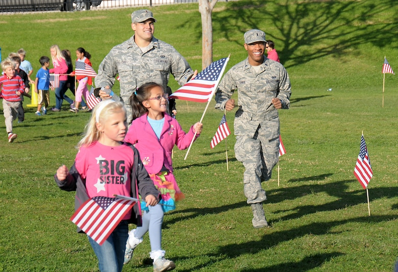 Lieutenant Francisco Lugo and Lt. Berkley Davis run with students from Jefferson Elementary School's Running Club, Nov. 9.  The students in the club run, skip, hop or walk for 20 minutes every day and earn points which can be used for prizes and other incentives.  (Photo by Joe Juarez)