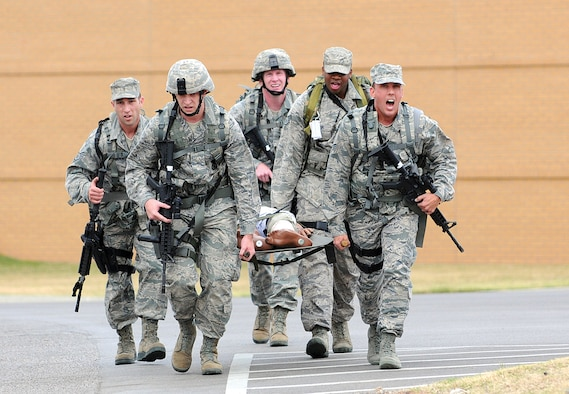 After a half-mile uphill litter carry race in the Self-Aid/Buddy Care challenge, the 507th Air Refueling Wing Security Forces Squadron team wills themselves to the finish line during the Nov. 10 Defender Challenge competition. Six teams from Tinker's 72nd Security Forces, Altus' 97th SFS and Tinker's 507th ARW/SFS were pushed to the limits in various combat skills during the first event of its kind here since the 1980s. .  (Air Force photo by Margo Wright)