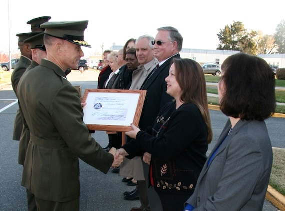 At Marine Corps Systems Command's (MCSC) 25th anniversary commemoration, Brigadier General Frank Kelley, MCSC Commander, presents Robyn Fait, Operations Manager for Marine Air-Ground Task Force Command, Control and Communications, with a certificate for continuously working for the Command since its establishment in November 1987.