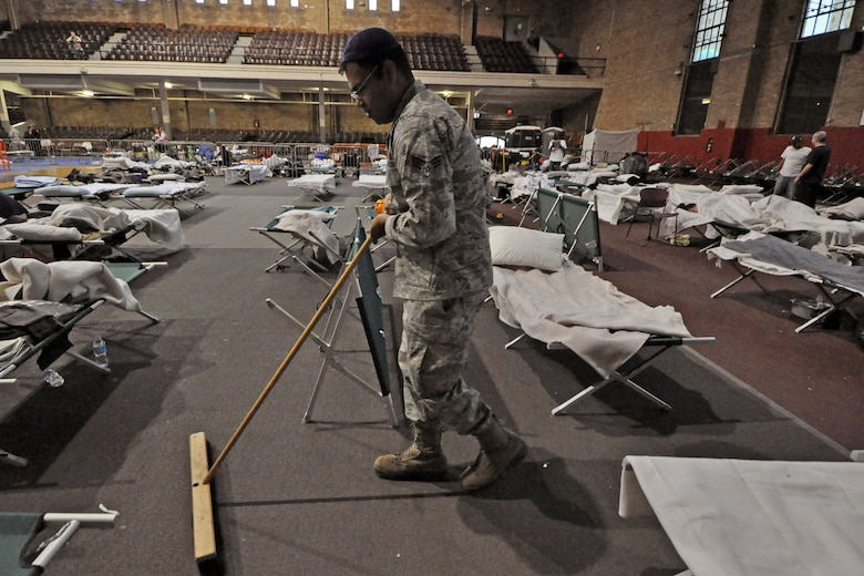 Senior Airman Mohammed Siddiqui, 108th Wing, sweeps the sleeping area for displaced residents at Jersey City, Nov. 7. The New Jersey National Guard is providing sheltering for displaced Jersey City residents at the Jersey City armory. (U.S. Air Force photo by Staff Sgt. Armando Vasquez/Released)