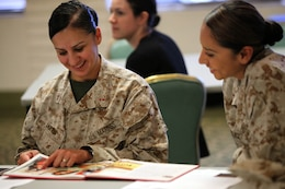 Chief Warrant Officer 3 Ernestina Jarvis (left) and Chief Warrant Officer 3 Sandra Gonzalez (right), personnel officers with Headquarters and Support Battalion, scan through a book during the first lady of the Marine Corps reading list kickoff and book review event here Oct. 29. Bonnie Amos, the commandant of the Marine Corps' wife, recommended a reading list so wives can gain insight and knowledge about the lifestyle of military spouses.The goal of the event was to have base residents get actively involved in reading the books and writing reviews for other potential readers.