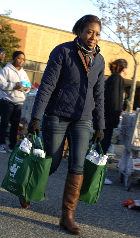 Master Sgt. Kendra Wilson, 30th Intelligence Squadron first sergeant, helps carry bags of Thanksgiving dinner; in support of Operation Warmheart Nov. 17, 2012, at Langley Air Force Base, Va. Money raised through 5K runs and donations allowed the Joint Base Langley-Eustis First Sergeant  ouncil to make roughly 550 food baskets for Airmen in need. (U.S. Air Force photo by Airman 1st Class R. Alex Durbin/Released)