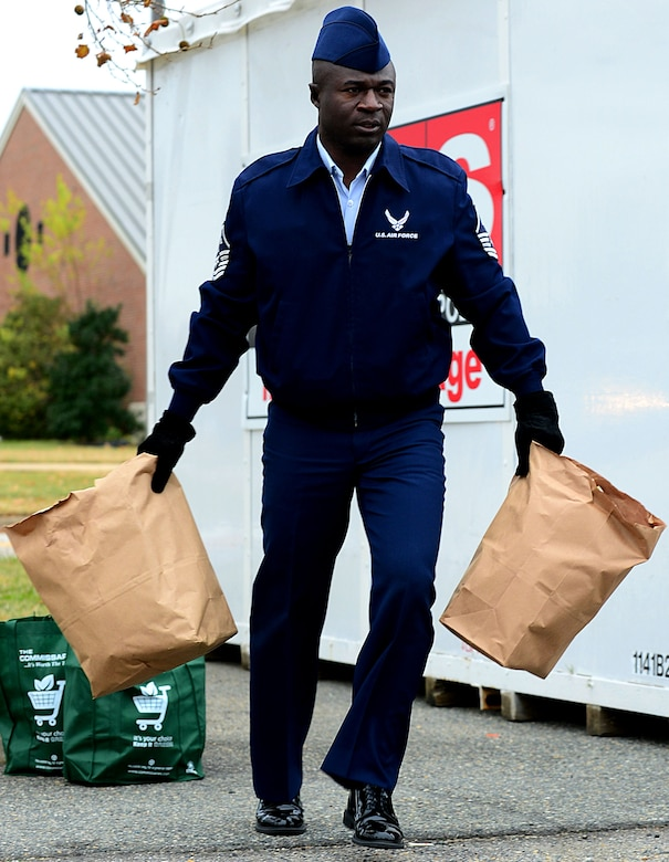 U.S. Air Force Master Sgt. Kenry Peart, 633rd Comptroller Squadron first sergeant, carries bags filled with groceries to a nearby car for distribution at Langley Air Force Base, Va., Nov. 19, 2012.  First Sergeants coordinate with supervisors to identify Airmen who would benefit most from the baskets that are donated through the Operation Warmheart program.  (U.S. Air Force photo by Airman 1st Class Kayla Newman/Released)