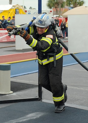 Air Force Academy firefighter Ron Prettyman hits a target with a stream from a firehose, during the over-40 relay team competition at the World Firefighter Combat Challenge XXI Nov. 17, 2012. The Air Force Academy's over-40 team won the 2012 championship, which it won previously in 2009. (U.S. Air Force photo/John Van Winkle)