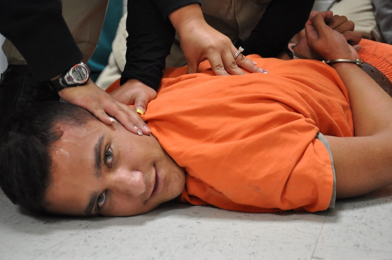 2nd Lt. Cody Gutierrez, from the Laughlin Air Force Base, Texas, is forced to the ground and handcuffed by Val Verde County prison staff, during a mock prison riot Nov. 14, 2012. The live exercise was designed to give the guards and medical staff hands-on training as if a real prison incident had occurred. (U.S. Air Force Photo/2nd Lt. David Tart)