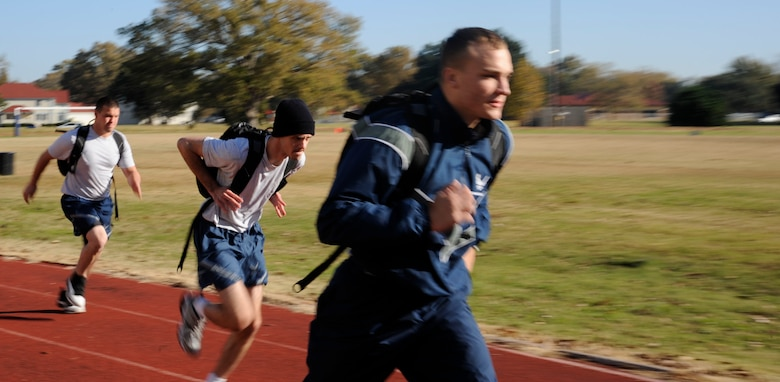Barksdale Airmen run around the track during a rucksack relay race as a part of the 2012 Sports Day on Barksdale Air Force Base, La., Nov. 16. This annual event gives Airmen the opportunity to participate in several individual and team sports throughout the day boosting morale. (U.S. Air Force photo/Airman 1st Class Andrew Moua)(RELEASED)