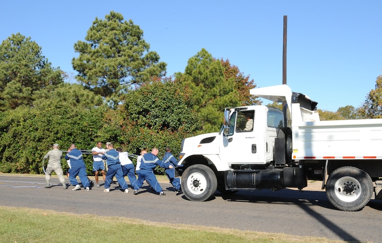 Airmen from the 2nd Civil Engineer Squadron pull a dump truck during the 2012 Sports Day on Barksdale Air Force Base, La., Nov. 16. Sports Day consisted of various team events including dodgeball, basketball, soccer, tug-of-war, volleyball, a homerun derby, flag football and racquetball. This day was designed to improve teamwork, and help increase the awareness of fitness, sports programs and boost morale. (U.S. Air Force photo/Airman 1st Class Benjamin Gonsier)(RELEASED)