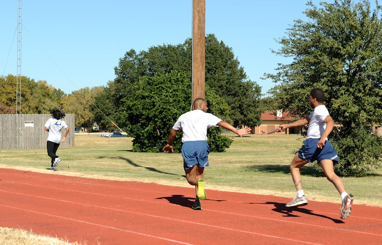 A Barksdale Airman passes off a baton during the 4x100 relay race and part of the 2012 Sports Day on Barksdale Air Force Base, La., Nov. 16. Sports Day consisted of various team events including dodgeball, basketball, soccer, tug-of-war, volleyball, a homerun derby, flag football and racquetball. This day was designed to improve teamwork, and help increase the awareness of fitness, sports programs and boost morale. (U.S. Air Force photo/Airman 1st Class Benjamin Gonsier)(RELEASED)