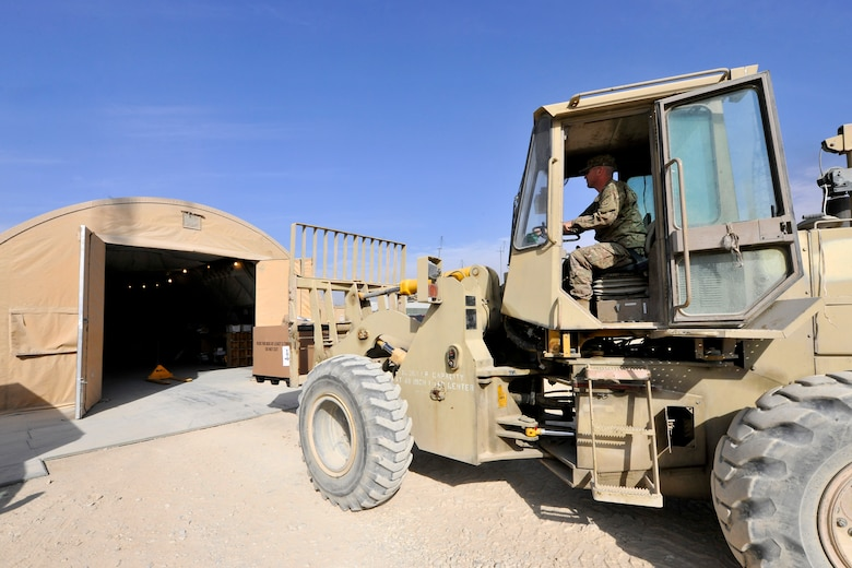 Tech. Sgt. Nathan Talavera, a member of the 455th Expeditionary Knowledge Operations Management office, carefully lowers a container of mail onto the receiving area of the postal annex at Bagram Airfield, Afghanistan, Nov. 15, 2012.  BAF Airmen receive an average of 18 containers of mail per day and more than 35 containers during the holiday season. (U.S. Air Force photo/Senior Airman Chris Willis)