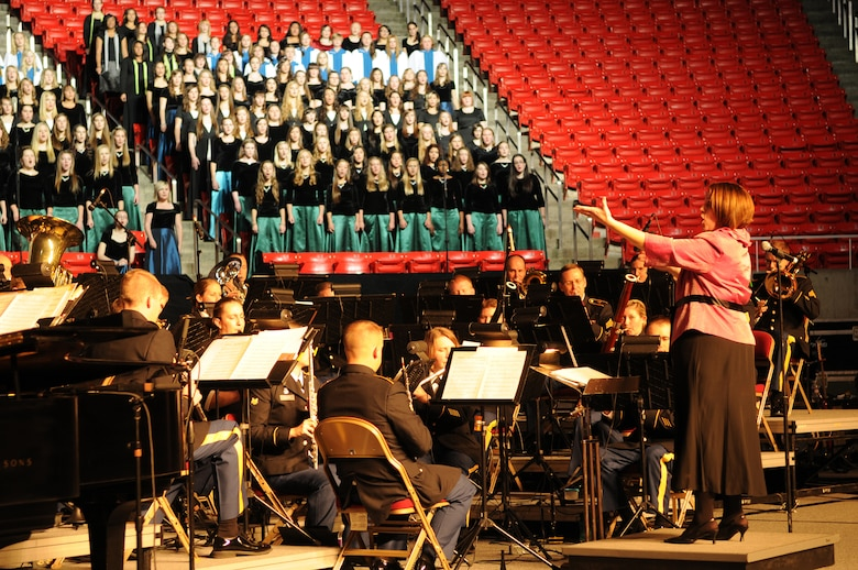 """Leah Tarrant conducts """"America, the Dream Goes On"""" with the 23rd Army Band and a 600-voice combined choir from Granite School District high schools. The production was part of the Utah National Guard's 57th annual Veterans Day concert at the University of Utah's Jon M. Huntsman Center, Nov. 10. (U.S. Air Force photo by Senior Airman Lillian Harnden)(RELEASED)"""