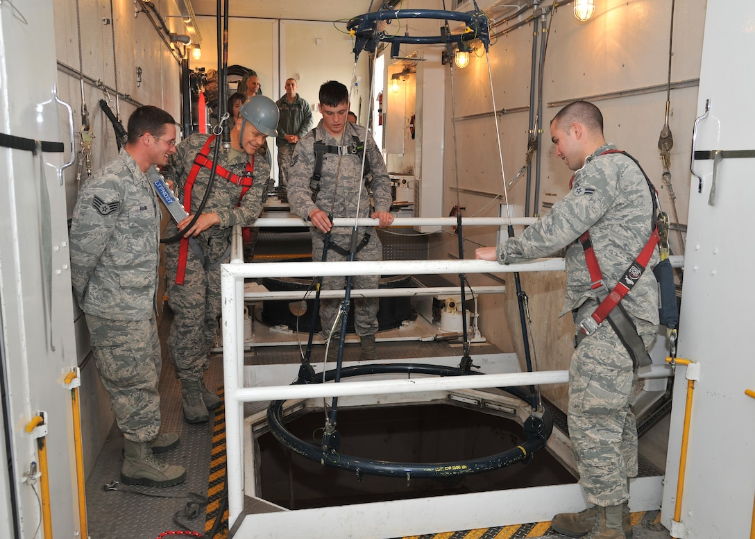 Chief Master Sergeant of the Air Force James Roy operates the hoist inside a Minuteman Payload Transporter III van, Nov. 20 at the T-9 maintenance trainer. Staff Sgts. Michael Adams and Michael Johnson, 341st Maintenance Operations Squadron team trainers, and Airman 1st Class Thomas Dekowski, a 341st Missile Maintenance Squadron tool room technician, observe and prepare to stow reentry system handling gear for transport. (U.S. Air Force photo/John Turner)