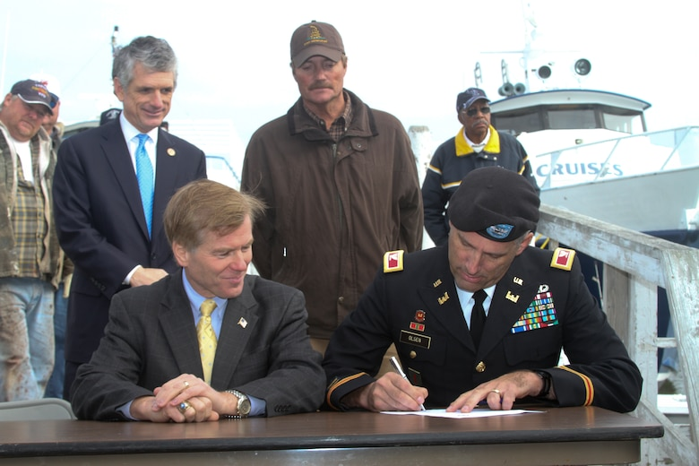 """TANGIER ISLAND, Va. -- From left, Congressman Scott Rigell, Gov. Bob McDonnell and Tangier's mayor, James """"Ooker"""" Eskridge, look on as Col. Paul Olsen, Norfolk District commander, signs a proclamation Nov. 20, 2012. The governor and the U.S. Army Corps of Engineers recently announced plans to build a long-awaited jetty to protect the island's endangered harbor. With the Corps' agreement several weeks ago to commit federal funds, a cost-sharing agreement with the Commonwealth was signed and the project approved for study, design and construction. (U.S. Army photo/Kerry Solan)"""