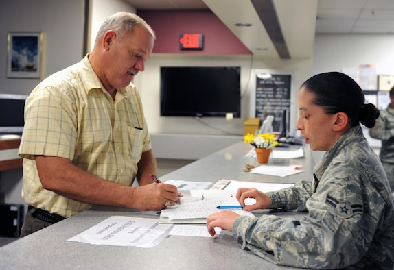 WHITEMAN AIR FORCE BASE, Mo. -- Airman 1st Class Melissa Malcolm, 509th Comptroller Squadron customer service representative, assists a customer with a travel voucher form. The 509th CPTS Financial Services Office provides a broad-based financial service to all service members and civilians, one of which is travel pay assistance. (U.S. Air Force photo/Heidi Hunt) (Released)