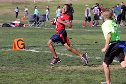 Isaiah Cole, 10, sprints for a touchdown, contributing to the Warrior's victory of 22-0 at the Buddy Bowl flag-football tournament here Nov. 24. The Buddy Bowl is a non-profit organization, which raises money for military families and civilian first-responders.