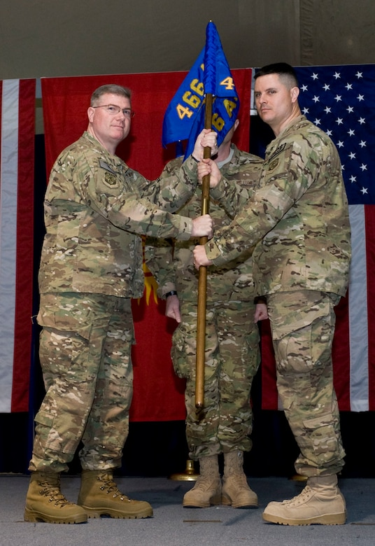 Col. John Cline, left, 466th Air Expeditionary Group commander passes the newly activated 466th Air Expeditionary Squadron guidon to Lt. Col. Joshua Hetsko, incoming commander, during an activation and asssumption of command ceremony, Transit Center at Manas, Kyrgyzstan, Nov. 26, 2012. Hetsko?s new squadron will assist the 466 AEG?s mission to provide administrative support and accountability for more than 2,300 Joint Expeditionary Tasking Airmen and Individual Augmentees serving throughout Afghanistan. (U.S. Air Force photo/Senior Airman Stephanie Rubi)