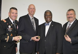 Kansas City, Mo., Mayor Sly James (second from right) presents coins to (left to right) Col. Anthony J. Hofmann and John D. Holm of the U.S. Army Corps of Engineers and John L. Robinson of SVS, Inc. on Nov. 28, 2012, as part of an awards presentation for the Blue River Project. The project won the Alphonse J. Dell'Isola Award for outstanding Value Engineering accomplishments from SAVE International. U.S. Army Corps of Engineers photo by Diana McCoy