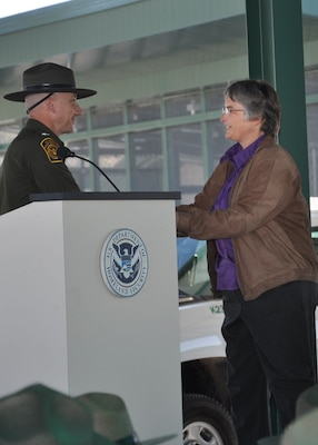 WHY, Ariz. -- Shari Brandt, resident engineer for the U.S. Army Corps of Engineers Los Angeles District's Tucson Resident Office, accepts a plaque of appreciation for the work done by the Corps from Jack Jeffreys, U.S. Customs and Border Protection patrol agent in charge of the Ajo Station, during a Nov. 27 ribbon-cutting ceremony at the station. The District served as the managing agent during construction of the new facility.