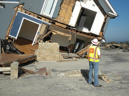 Doug Weber, infrastructure assessment action officer, U.S. Army Corps of Engineers, Seattle District, looks at building damages, Mantoloking, N.J., during an infrastructure assessment after Hurricane Sandy. The Corps of Engineers Infrastructure Assessment Planning and Response Teams (IA-PRTs) augment local efforts to inspect buildings that are primarily residential, and to manage inspections of public works facilities following a major disaster, as assigned by FEMA. The IA mission is intended to be highly flexible and scalable in order to meet the specific and changing needs of impacted communities during response and recovery efforts.